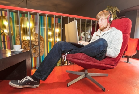 Young man on laptop sitting in lounge