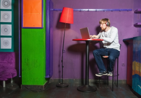 Young man sitting working on laptop in colourful location photo