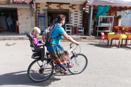 winter escape: DAHAB, EGYPT - JANUARY 29, 2011  Russian woman on a bicycle with daughter on January 28, 2011 in Dahab, Egypt  Hundreds of Russian families come to Egypt in winter to escape the cold