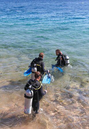 dahab: DAHAB, EGYPT - JANUARY 24, 2011: Divers enter the sea on January 24, 2011 in Dahab, Egypt. Blue Hole is a popular diving location on east Sinai. Editorial