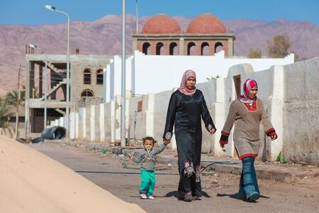 DAHAB, EGYPT - FEBRUARY 2, 2011: Women in traditional dresses walking with child on February 2, 2011 in Dahab, Egypt. Hijab is a veil which covers the hair and neck.