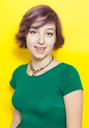 Cute modern and urban looking girl smiling on yellow background photo