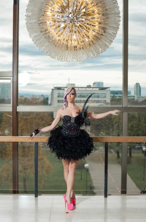 Young female performing in pink high heels and feather dress photo