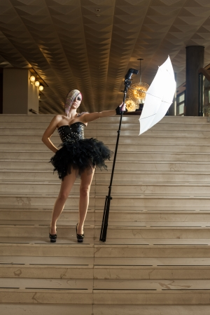 Young woman in feather dress standing on stairs with flash photo