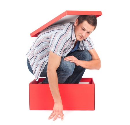 Young man in a box, seems stuck in his thoughts  Stock Photo - 17018541