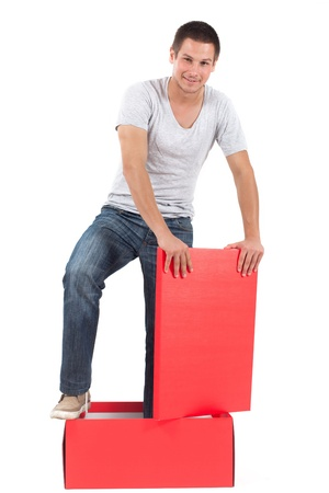 Out of the box, young man standing in a red box, ready to get out. Stock Photo - 16617743