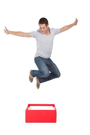 Think out of the box: young man jumping out a red box. Stock Photo - 16617736