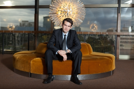 Young corporate executive sitting in luxurious interior photo