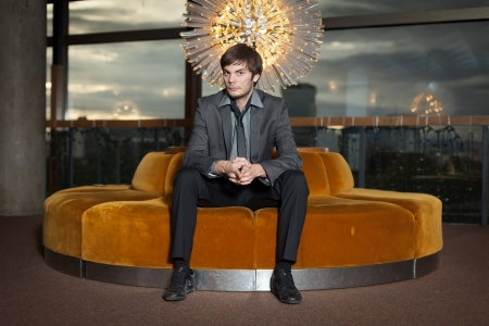 old sofa: Young corporate executive sitting in luxurious interior