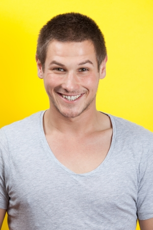 Handsome young man smiling in yellow background Stok Fotoğraf