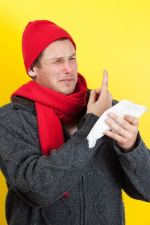 hanky: Ill young man with red nose, scarf and cap picking nose with hanky Stock Photo