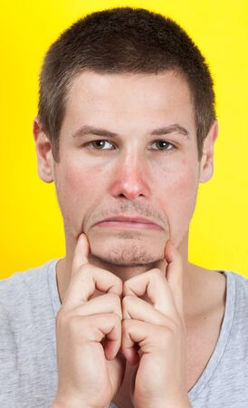 woeful: Sad man making unhappy face with hands