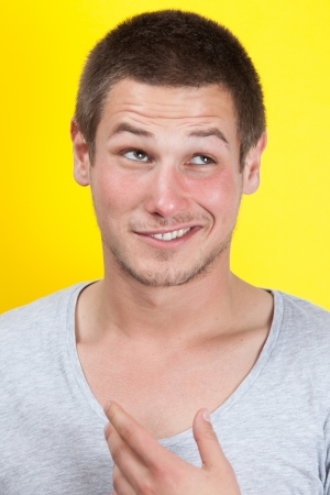 Man with a cheeky face on yellow background Stock Photo - 16623047