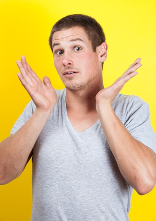 Surprised young man with hands in air, on yellow background Stock Photo - 16637297
