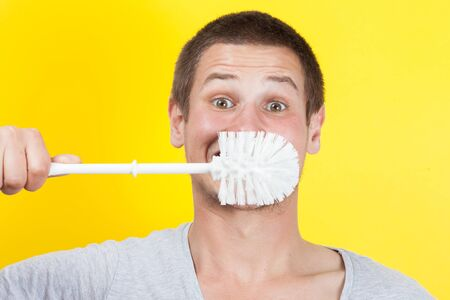 Young man brushing teeth with toilet brush