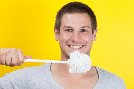 Young man brushing teeth with toilet brush photo