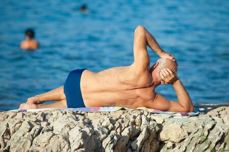 SPLIT, CROATIA - August 25, 2012: Older man sunning at he beach on August 25, 2012 in Split, Croatia. Split is the second largest city in Croatia. Stock Photo - 16817014
