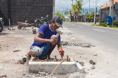 BALI - FEBRUARY 19: Man working on roadside on February 19, 2012 in Bali, Indonesia. Bali's construction industry is in full boom with much foreign investment on the island.