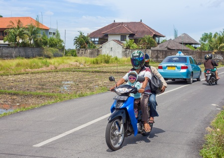afford: BALI - FEBRUARY 19: Local Balinese family on scooter on February 19, 2012 in Bali, Indonesia. Most Balinese people cannot afford cars and drive with motorcycles. Editorial