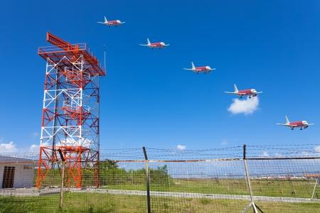 multiple exposure: Rosso e bianco torre radar in metallo nella zona di aeroporto con aereo di atterraggio esposizione multipla