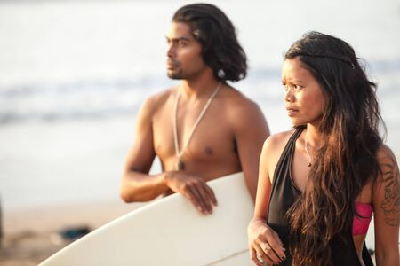 Young multi-ethnic couple on beach with surfboard in the tropics photo
