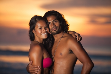 Young multi-ethnic couple on romantic beach at sunset in the tropics photo