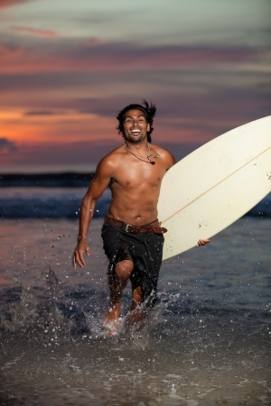 Handsome multi-ethnic man running in waves with surfboard photo