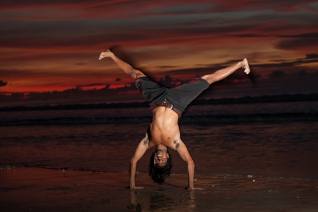 Young man doing capoeira on beach at sunset Stock Photo - 17260034