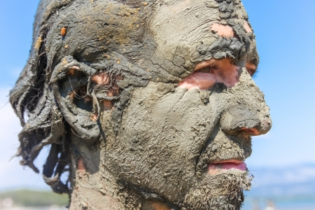 Man smeared with healing mud on beach Stock Photo - 17085492