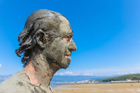 Man smeared with healing mud on beach Stock Photo - 17085488