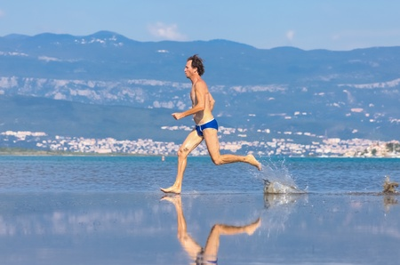 Man run across the beach in blue bathing suit Stock Photo - 17085484