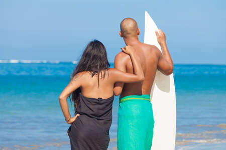 Young couple looking at surf with surfboard on beach photo