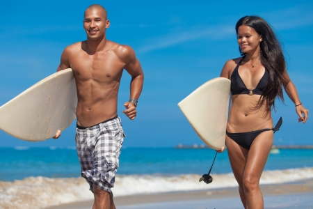 Young couple running on beach with surfboards in arm photo