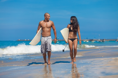 surfing beach: Young couple walking on beach with surfboards in arm