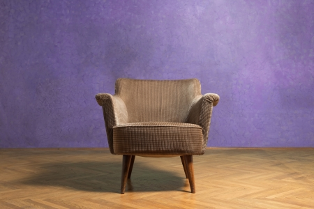Old chair in grunge room with purple wall photo