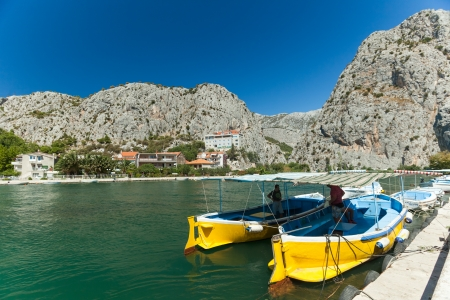 OMIS, CROATIA - AUGUST 28, 2012: Men in boats on the River Cetina on August 28, 2012 in Omis, Croatia. Cetina River empties into the sea in Omis.