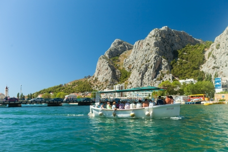 OMIS, CROATIA - AUGUST 28, 2012: People in boat  going on the tour on the River Cetina on August 28, 2012 in Omis, Croatia. Cetina River empties into the sea in Omis.