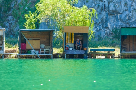 OMIS, CROATIA - AUGUST 28, 2012: People in fishing lodges on the River Cetina on August 28, 2012 in Omis, Croatia. Cetina River empties into the sea in Omis. Editorial