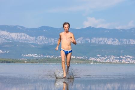 Man run across the beach in blue bathing suit Stock Photo - 18714925