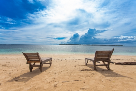 deck chairs: Wooden lounger on lonely beach in the tropics Stock Photo