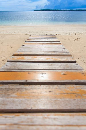 Wooden jetty on tropical beach on island photo