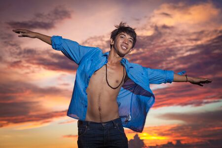 Young asian man jumping at sunset Stock Photo - 18737020