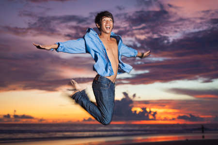 Young asian man jumping at sunset Stock Photo - 18735055