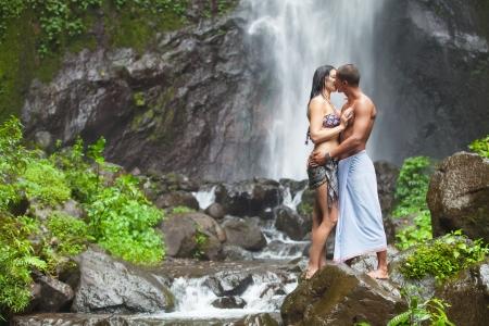 people kissing: Jeune couple profitant de la fra�cheur de la nature sous une cascade dans les tropiques Banque d'images