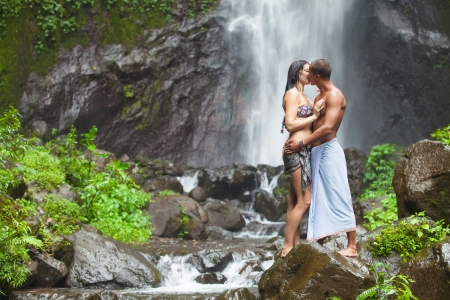 women kissing: Young couple enjoying the freshness of nature under a waterfall in the tropics