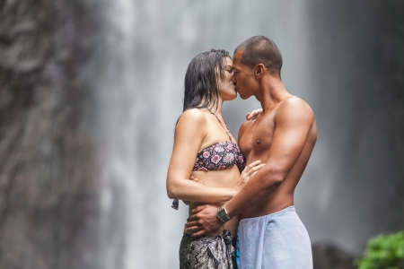 man waterfalls: Young couple enjoying the freshness of nature under a waterfall in the tropics