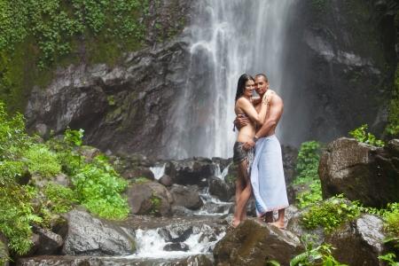 Junges Paar genießt die Frische der Natur unter einem Wasserfall in den Tropen Standard-Bild - 18737016
