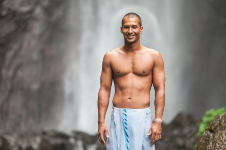 pectorals: Young handsome man enjoying waterfall in the tropics Stock Photo