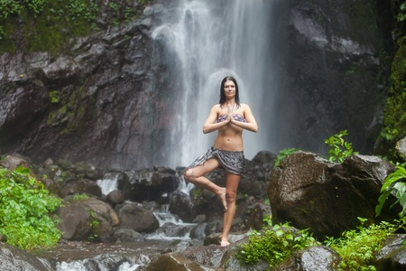 Young beautiful caucasian woman enjoying yoga under waterfall in the tropics photo