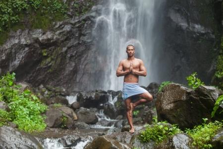 man waterfalls: Young handsome man enjoying  yoga at waterfall in the tropics Stock Photo
